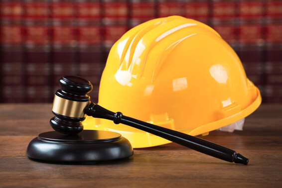 Closeup of wooden mallet and yellow hardhat on table in courtroom
